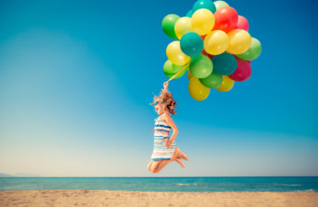 Happy child jumping with colorful balloons on sandy beach